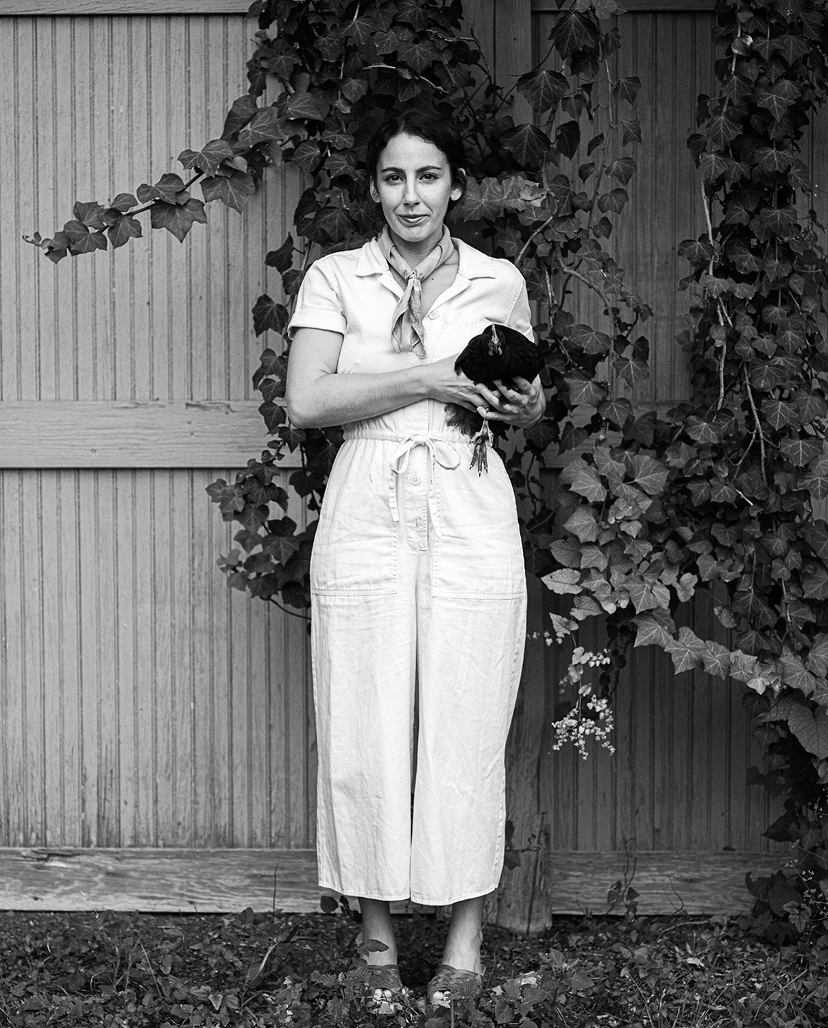 Gabriela Santiago holds a chicken for a portrait by conceptual photographer Josh Huskin.